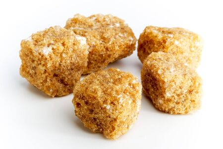 Brown sugar cubes. Pieces of brown cane sugar on light background