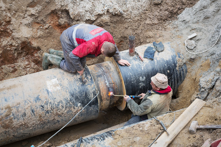 Odessa, Ukraine - October 11, 2016: Repair of heating duct. The workers, welders made by electric welding and gas welding on large iron pipes at a depth of excavated trench. Editorial