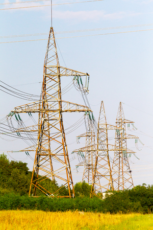 electric grid: High-voltage lines and power transmission pylons in the flat and green agricultural landscape on a Sunny day in the blue sky without clouds.