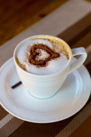 Cup of fresh coffee. Fresh coffee for morning breakfast on wooden background. The pattern of the heart.