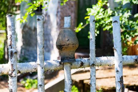 Birch fence. Hanging on fence of clay utensils. Abandoned city Chernobyl radioactive contamination. Consequences of looting and vandalism after an explosion. People left city during disaster