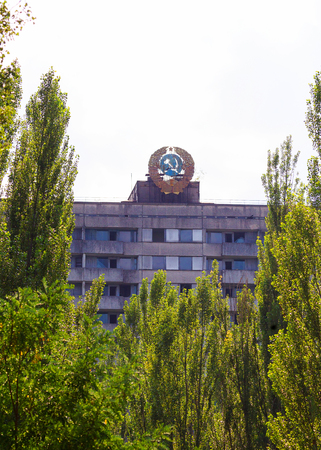 Emblem of USSR on roof of building. Abandoned city Chernobyl radioactive contamination. Consequences of looting and vandalism after an explosion. People left city during disaster