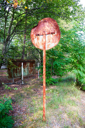 yellow beware: Old rusty metal signs in the Chernobyl zone. Radioactive area. Warning about dangerous area