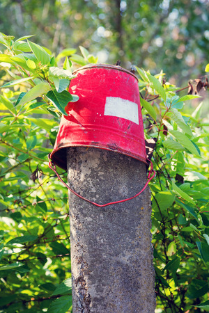 Red iron bucket hanging on concrete pillar. Old rusty metal signs in the Chernobyl zone. Radioactive area. Warning about dangerous area