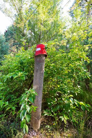 dangerous work: Red iron bucket hanging on concrete pillar. Old rusty metal signs in the Chernobyl zone. Radioactive area. Warning about dangerous area