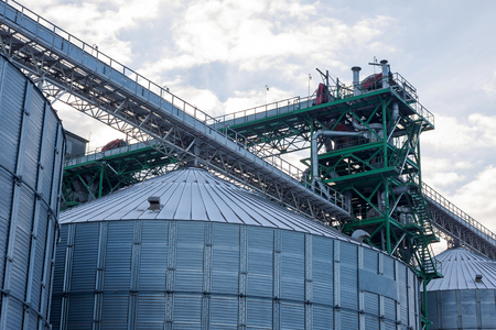 Metal grain elevator in agricultural zone. Agricultural Silos. Building Exterior. Storage and drying of grains, wheat, corn, soy, sunflower on background of cloudy sky. Agriculture. Stock Photo