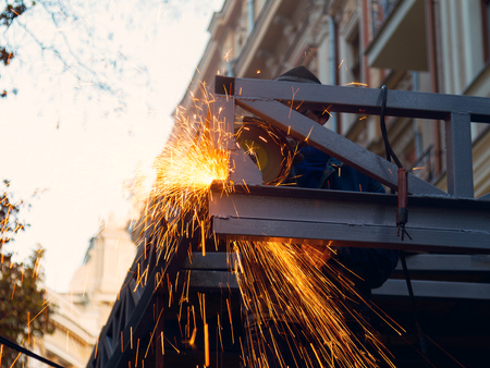 Worker cutting metal with grinder. Sparks while grinding iron. Low depth of focus