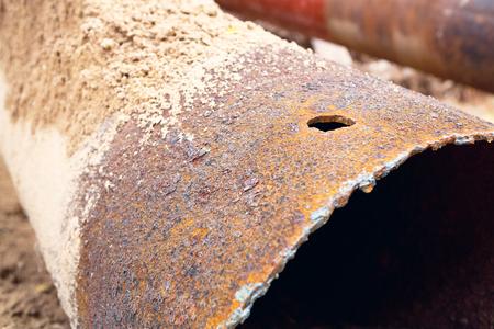 Fragmenten van oude grote waterpijpen. Na vele jaren van operatie is gecorrodeerde metalen pijp vernield. Roestige stalen buis met gaten metaalcorrosie. Selectieve aandacht. Stockfoto - 84979633