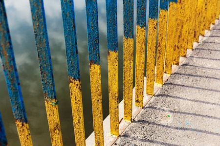 Fence on bridge. Background of rusty iron rods. Painted with blue and yellow paint. As background for your art design.