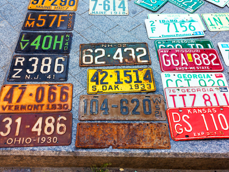 Odessa, Ukraine - circa 2017: car numbers from around the world on display. Discontinued the license plate of cars from cars of Europe and the United States on the paving tiles. Vintage background antique license plates of Europe and the States