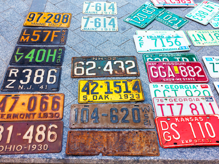 old photo: Odessa, Ukraine - circa 2017: car numbers from around the world on display. Discontinued the license plate of cars from cars of Europe and the United States on the paving tiles. Vintage background antique license plates of Europe and the States