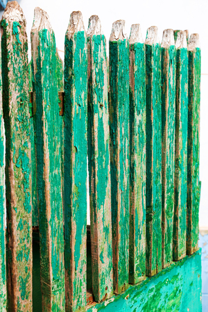 private security: Fence. Wooden fence around the village houses, painted with green paint. Rural landscape.