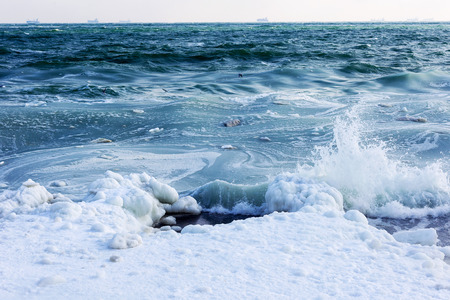 Winter seascape. Snow, ice huge waves beating against the shore and freezes. Natural disaster in form of storms and severe frosts led to icing of the black sea coast near Odessa. Stock Photo