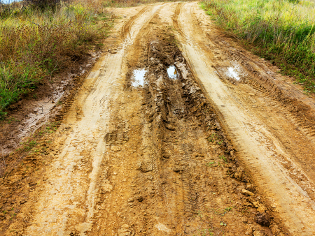 Traces of off-road tires. Cracked earth on country road with traces of tires, cars, cracks and dirt. To use as background. Stock Photo