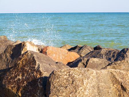 Seascape, background granite and the sea in haze. Waves breaking on huge granite stones Stock Photo