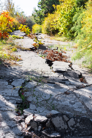 Huge cracks on pavement due to natural disasters, landslide, earthquake. Broken coating of asphalt leading to pothole, dangerous for vehicles pedestrians. Of poor road emergency situations.