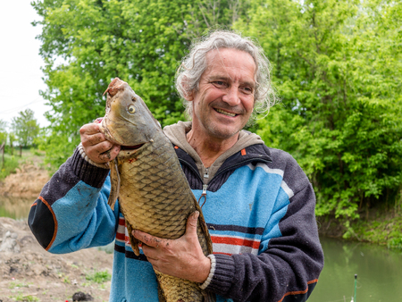 Man fisherman caught a large freshwater carp. Fisherman with trophy on the banks of the river