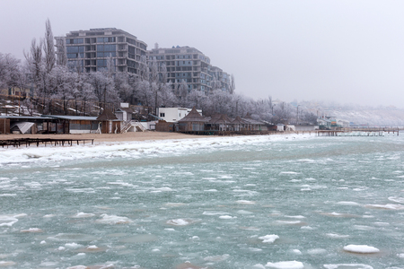 Sea covered with broken ice. Black sea in winter. On horizon, city buildings are visible in haze.