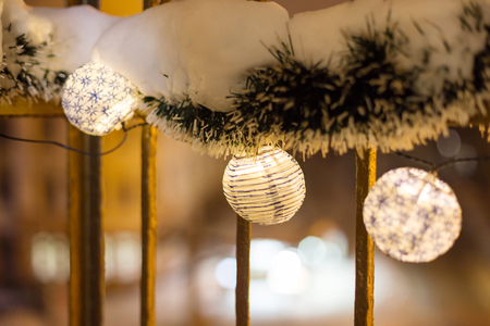 New Year's burning lanterns and tinsel under the snow on blurred background, as background for your Christmas project. Selective soft focus