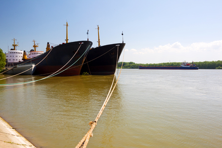 Barges on dock of river port on Danube River, shipping.