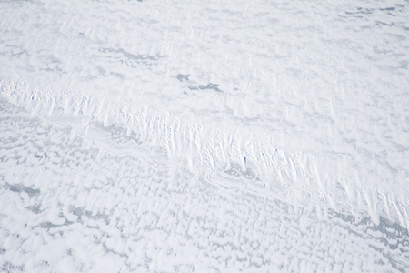 Ice covered with white snow as an abstract winter background