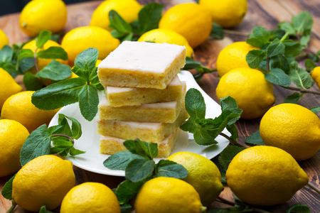 Sliced shortcake, many lemons and mint on wooden table