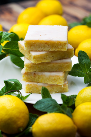 Sliced shortcake, many lemons and mint on wooden table