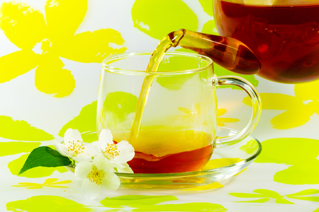 Jasmine flowers and tea are poured into transparent cup from glass teapot on an abstract floral background