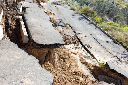 Broken road asphalt cracked and shifted by landslide after earthquake. Landslide caused by torrential rains of Hurricane CHRISTIE.