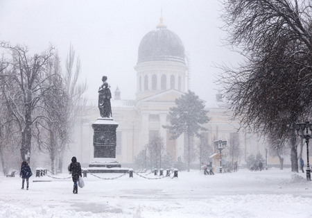 Winter city landscape. People on the streets of the city during snowfall.