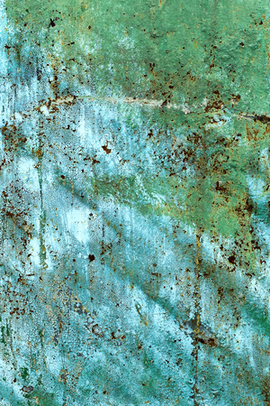Creative background of rusty metal, painted gray paint carelessly with the remnants of torn paper. Grungy metal surface. Great background or texture for your project.