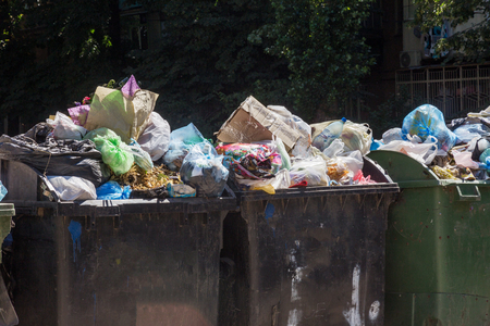 Overcrowded garbage containers with rubbish. Disused solid household garbage on road. Environmental pollution. Ecological problem. Abandoned garbage on road. Problem of waste management in a big city Stock Photo