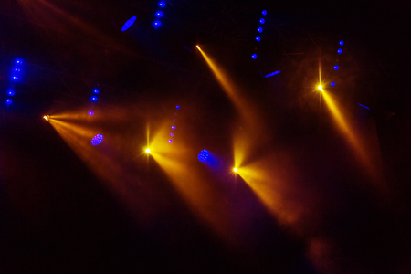 Stage lights. Several projectors in dark. A bright colored spotlight permeates the darkness. Light from the stage, rock concert. Lighting equipment. Several projectors on theatrical lighting system