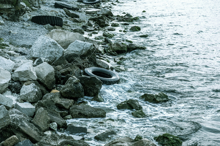 Used car tires remained in nature. The old unnecessary tire of car remained in the water. The problem of recycling waste, garbage, environmental pollution The environmental problem of waste management