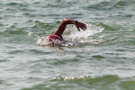 Swimmer swims in sea. Athlete triathlete swimmer drains from water. A professional athlete in triathletes trains for an ironman. The sportsman beautifully floats in blue sea water at competitions