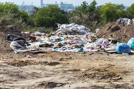 Pollution of the environment by people. Illegal garbage dump in the wasteland. A pile of household garbage in a dump in bags. A huge pile of waste extends to the garbage mountain Stock Photo