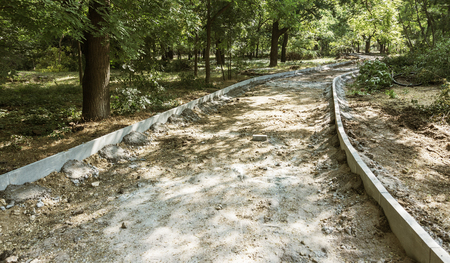 building a new path in a summer park. Marking, repair and reconstruction of the pedestrian walkway in the city park 免版税图像