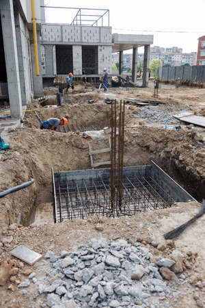 ODESSA, UKRAINE - September 5, 2018: Workers on construction site make cement foundation for housing construction Foundation construction site making reinforcement metal framework for pouring concrete