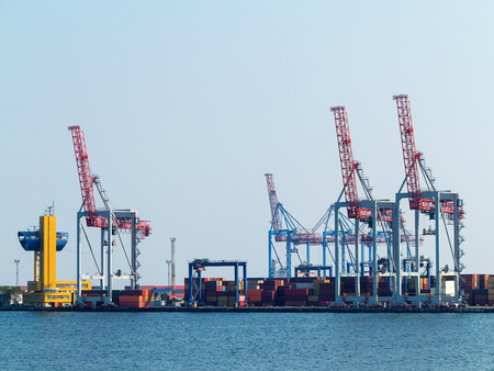Large cranes for loading goods on large marine cargo ships at the container terminal in the port of Odessa sea port on a foggy day