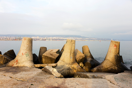 The storm surge barrier breakwater. Concrete block breakwater in port. Sea landscape.