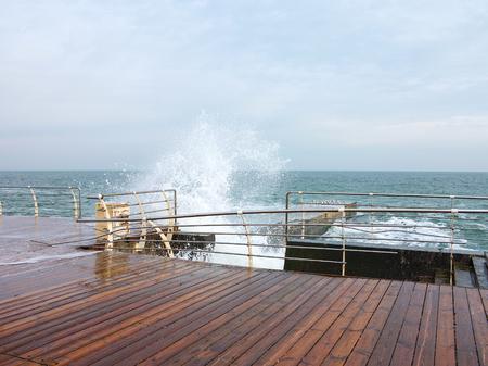 Huge stormy waves crashing near city embankment, dramatic sky