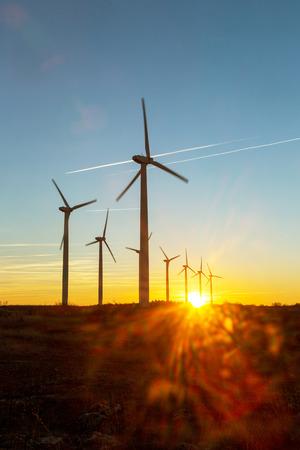 Windkraftanlagen in der Abenddämmerung. Landschaftssonnenuntergang mit Windmühlen. Erneuerbare Stromquelle. Windturbinen setzen neue Technologie für saubere Energie auf den Bergen ein, Blick auf den Sonnenuntergang mit farbenfroher Dämmerung am Himmel Standard-Bild