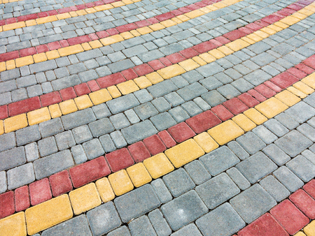 Close-up paving slabs by mosaic. Road paving, construction. Tessellated sidewalk tile. Colored concrete paving slab.