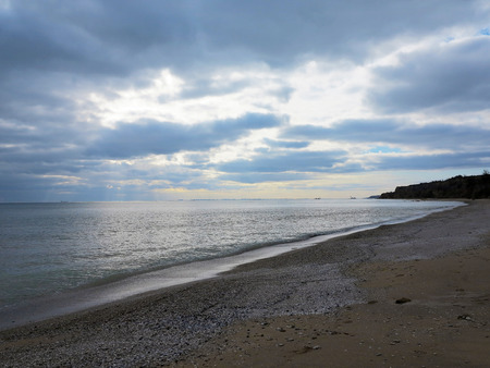 Beautiful panoramic seascape. Embankment of the Black Sea near Odessa. Calm sea against the gloomy sky with rays of sunlight breaking through the clouds.