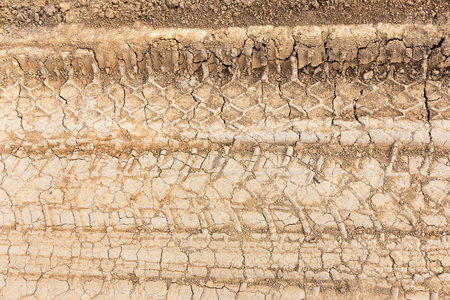 Tyre track and human footprint on sand texture background. Traces of off-road tires. Cracked earth on country road with traces of tires, cars, cracks and dirt. To use as background