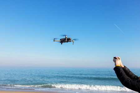 Drone with camera flies over the sea against a blue cloudless sky
