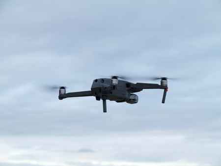 Drone with camera flying over blue sky background Stock Photo
