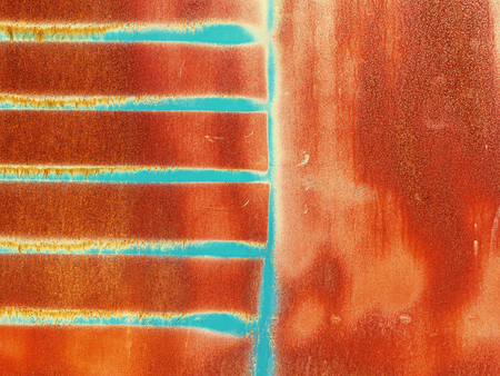 Bright multi-colored paint on rusty metal surface. Rusty metal wall, old sheet of iron covered with rust with multi-colored paint. As textured authentic background for your project 免版税图像