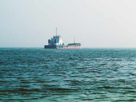 Old cargo ship goes to the industrial and commercial port for cargo loading and further transportation. Shipping, Transportation, Logistic Import Export background Stock Photo