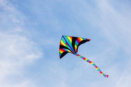 Colorful kite flying in the cloudy sky.